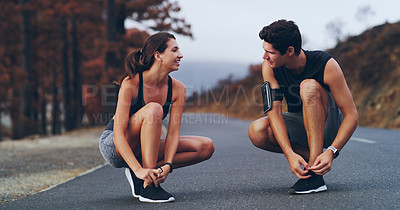 Buy stock photo Shot of a sporty couple tying their shoelaces before a run