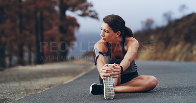 Buy stock photo Shot of a sporty young woman stretching before her run