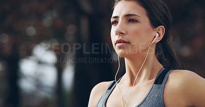 Buy stock photo Cropped shot of a young woman listening to music through her earphones while out exercising