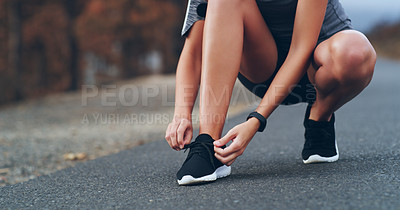 Buy stock photo Cropped shot of an unrecognizable woman tying her shoelaces while out for a run