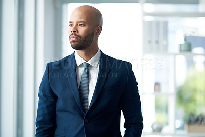 Buy stock photo Shot of a handsome young businessman looking away and deep in thought inside his office
