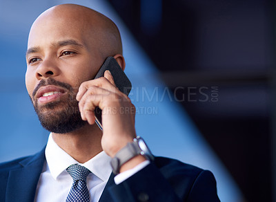 Buy stock photo Shot of a handsome young businessman taking a phone call while standing outside an office building
