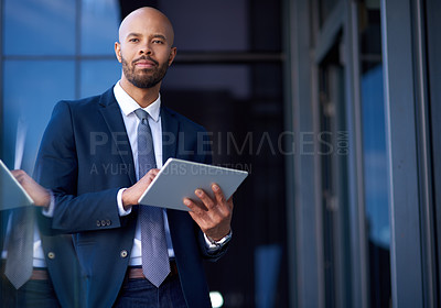 Buy stock photo Portrait of a handsome young businessman using a digital tablet while standing outside an office building