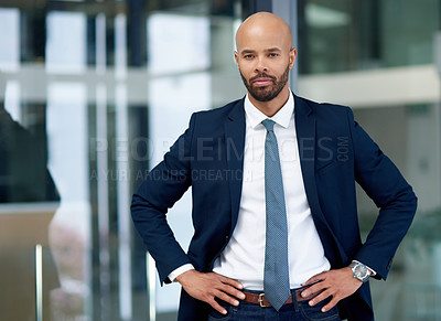 Buy stock photo Portrait of a handsome young businessman posing with his hands on his hips in his office