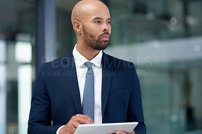 Buy stock photo Shot of a handsome young businessman using a digital tablet in his office