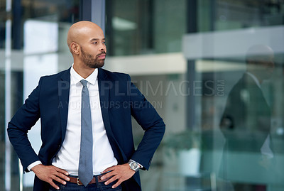 Buy stock photo Shot of a handsome young businessman posing with his hands on his hips in his office
