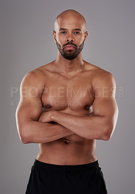 Buy stock photo Portrait of a handsome young athlete posing with his arms folded against a grey background