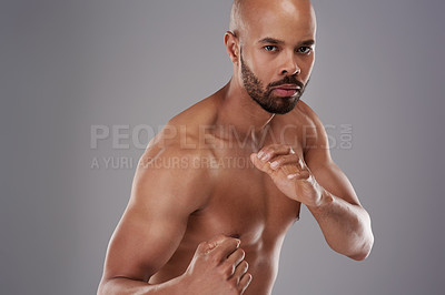 Buy stock photo Portrait of a handsome young athlete posing in fighting stance against a grey background