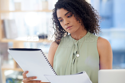 Buy stock photo Cropped shot of an attractive young businesswoman looking over paperwork while working at her desk in the office