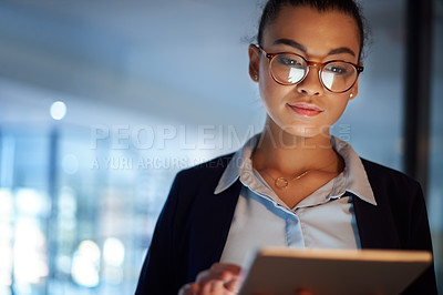 Buy stock photo Shot of a young businesswoman using a digital tablet in an office at night