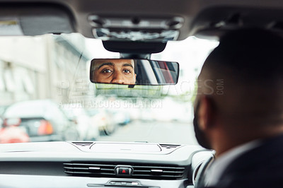 Buy stock photo Cropped shot of a man looking into his rearview mirror while driving