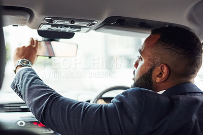 Buy stock photo Shot of a man adjusting his rearview mirror while driving