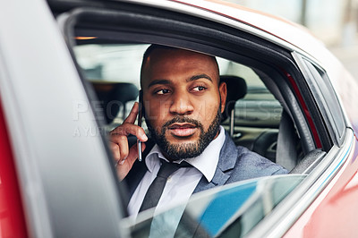 Buy stock photo Shot of a businessman talking on a cellphone while traveling in the backseat of a car