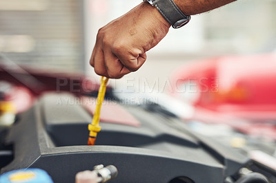 Buy stock photo Cropped shot of a man holding a dipstick while checking the oil in a car