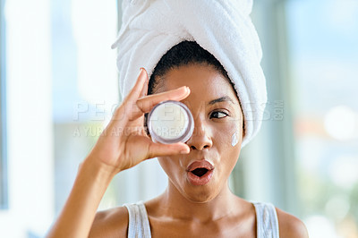 Buy stock photo Shot of an attractive young woman holding a tub of moisturiser in front of her eye during her beauty routine