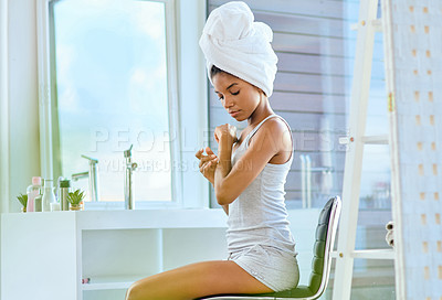 Buy stock photo Shot of an attractive young woman applying moisturiser to her arms during her morning beauty routine