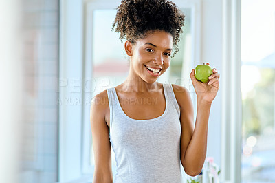 Buy stock photo Shot of an attractive young woman eating an apple during her morning routine