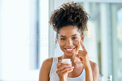 Buy stock photo Shot of an attractive young woman applying moisturiser to her face during her morning beauty routine