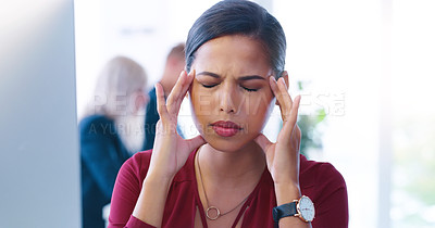 Buy stock photo Cropped shot of a stressed young businesswoman seated at her desk while suffering from a headache in the office