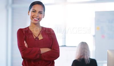 Buy stock photo Portrait of a confident young businesswoman standing with her arms folded inside of the office