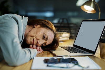 Buy stock photo Shot of a mature businesswoman falling asleep at her desk while working in an office at night