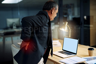 Buy stock photo Shot of a mature businessman suffering with back pain while working in an office at night