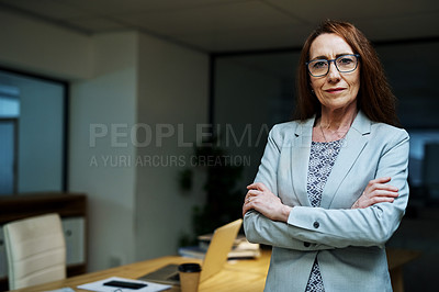Buy stock photo Portrait of a mature businesswoman standing with her arms crossed in an office at night