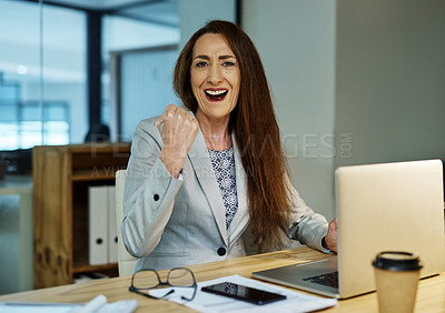 Buy stock photo Portrait of a mature businesswoman cheering while working on a laptop in an office at night