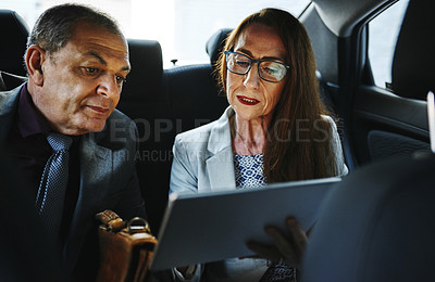 Buy stock photo Shot of two mature businesspeople using a digital tablet while travelling together in the backseat of a car