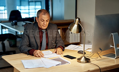 Buy stock photo Shot of a mature businessman going through paperwork in an office at night