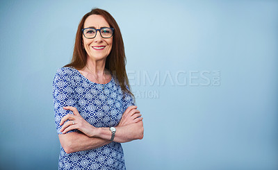 Buy stock photo Studio portrait of a mature businesswoman standing with her arms crossed against a grey background