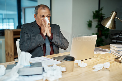 Buy stock photo Shot of a mature businessman blowing his nose while working in an office at night