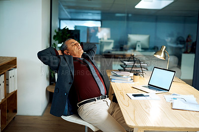Buy stock photo Shot of a mature businessman taking a break while working in an office at night