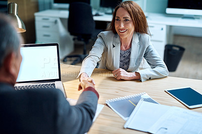 Buy stock photo Shot of a mature businesswoman shaking hands with a businessman in an office