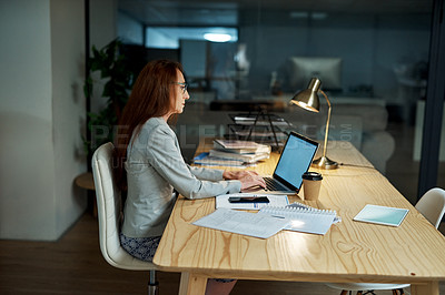 Buy stock photo Shot of a mature businesswoman using a laptop in an office at night