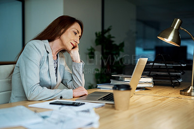Buy stock photo Shot of a mature businesswoman looking bored while working on a laptop in an office at night