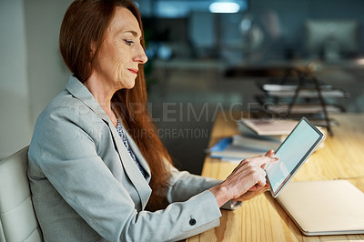 Buy stock photo Shot of a mature businesswoman using a digital tablet while working in an office at night