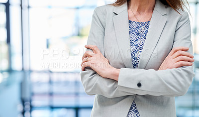 Buy stock photo Closeup shot of an unrecognizable businesswoman standing with her arms crossed in an office