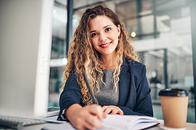 Buy stock photo Portrait of a young businesswoman writing notes in an office