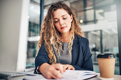 Buy stock photo Shot of a young businesswoman writing notes in an office