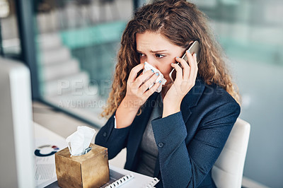 Buy stock photo Shot of a young businesswoman using a cellphone while blowing her nose in an office