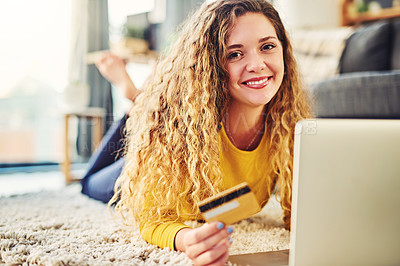 Buy stock photo Shot of a young woman using a laptop and credit card on the floor at home