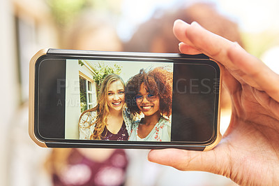 Buy stock photo Portrait of two cheerful young friends taking a self portrait together with a cellphone outside during the day