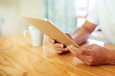 Buy stock photo Cropped shot of an unrecognizable person browsing on a digital tablet inside at home during the day