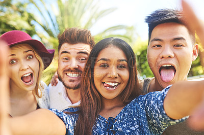 Buy stock photo Portrait of a group of cheerful young friends taking a self portrait together with a cellphone outside during the day