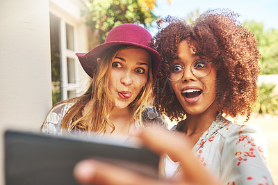 Buy stock photo Cropped song of two cheerful young friends taking a self portrait together outside during the day