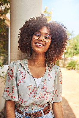 Buy stock photo Portrait of a cheerful young woman standing and leaning against a pillar outside during the day