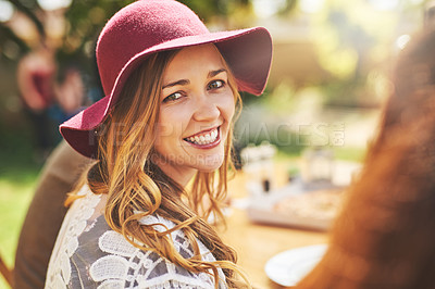 Buy stock photo Portrait of a cheerful young woman looking back at the camera while being seated at a lunch table outside during the day