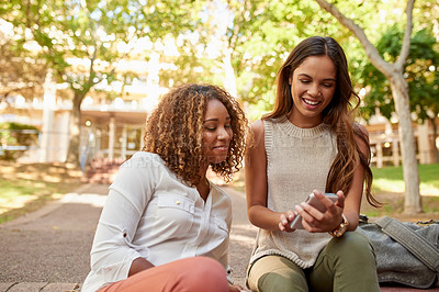 Buy stock photo Cropped shot of two attractive young female students using a smartphone together during their free time on campus
