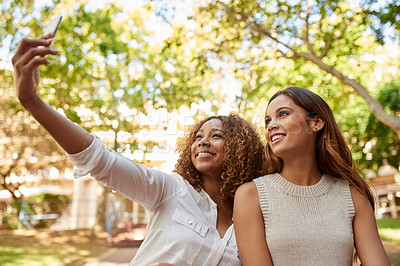 Buy stock photo Cropped shot of two attractive young female students taking a selfie together during their free time on campus